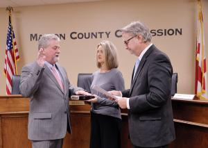 Keith Nichols (left) is shown being sworn in as Marion County District 1 Commissioner. His wife, Jan, is holding the Bible. District Judge Mark Hammitte conducted the ceremony.